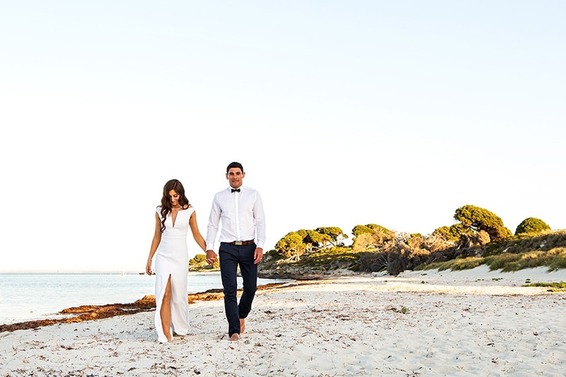 perth wedding photographer rottnest island wedding image of couple walking on rottnest beach holding hands