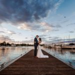 wedding photographer perth matilda bay wedding image of bride and groom standing on jetty at sunset surrounded by boats