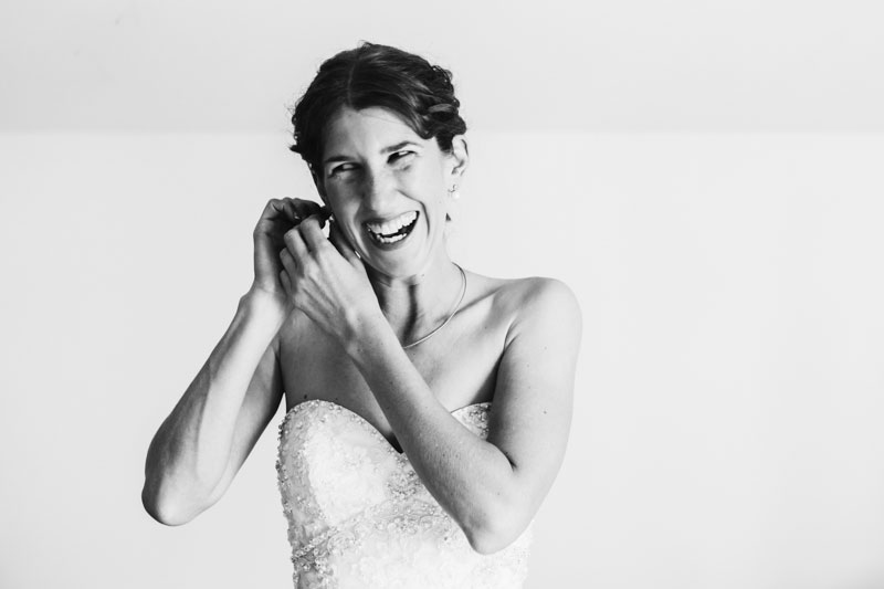south west wedding photographer image of bride putting earrings on
