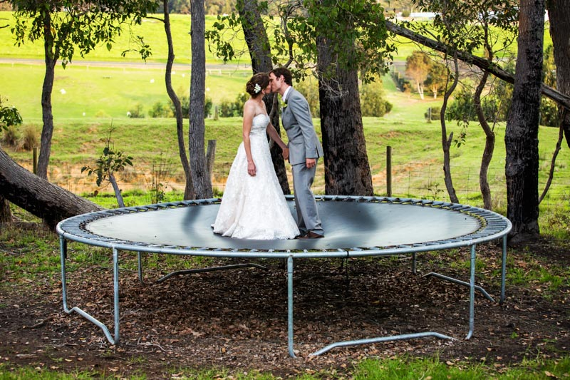 south west wedding photographer image of bride and groom kissing on trampoline