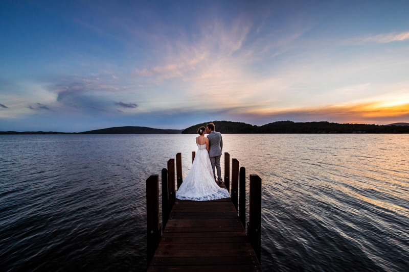 south west wedding photographer image of bride and groom on jetty at sunset