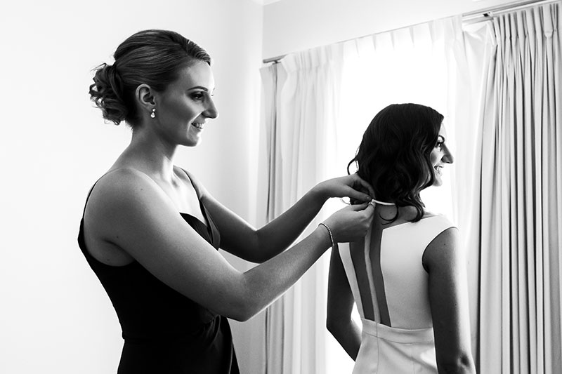 perth wedding photographer rottnest island wedding image of bride getting back of dress done up