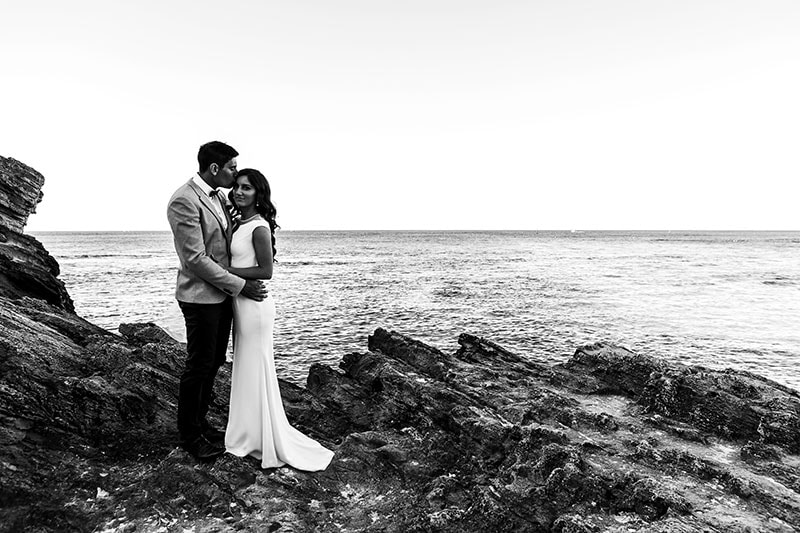 perth wedding photographer rottnest island wedding image of bride and groom standing on rocks on rottnest island