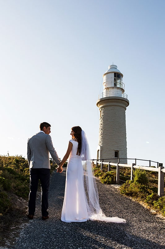 perth wedding photographer rottnest island wedding image of bride and groom standing near lighthouse on rottnest island