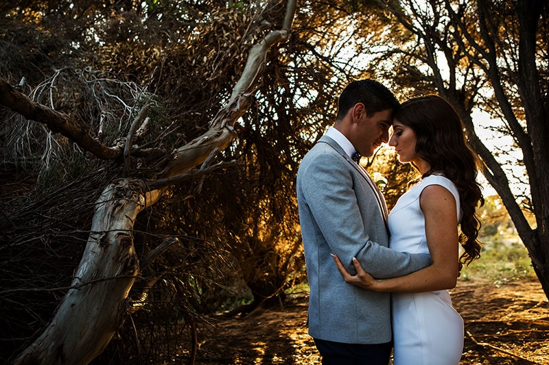 perth wedding photographer rottnest island wedding image of bride and groom hugging each other in golden light