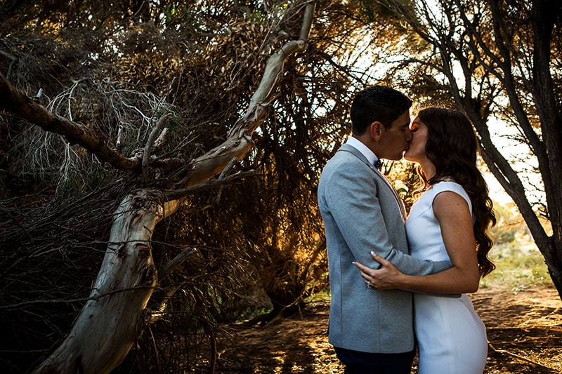 perth wedding photographer rottnest island wedding image of bride and groom kissing in golden light