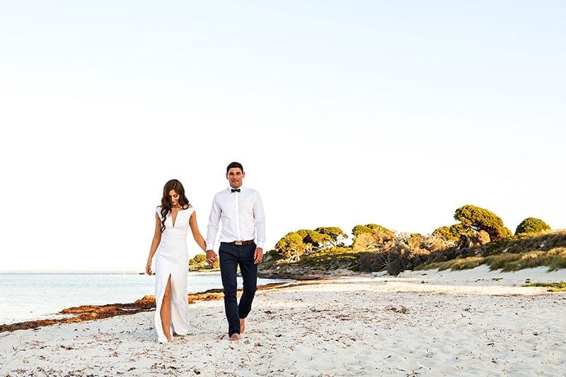 perth wedding photographer rottnest island wedding image of couple walking on rottnest beach holding hands