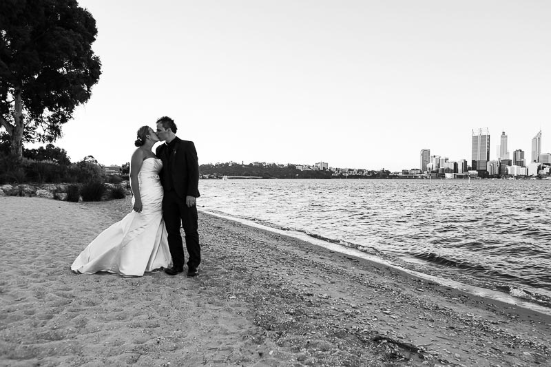 perth wedding photographer south perth wedding image of bride and groom kissing on river bank