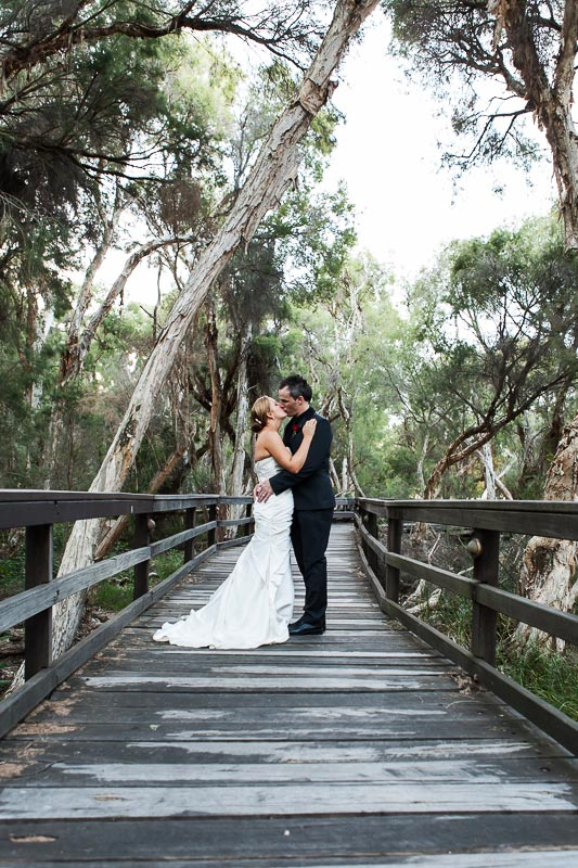 perth wedding photographer south perth wedding image of bride and groom kissing on board walk