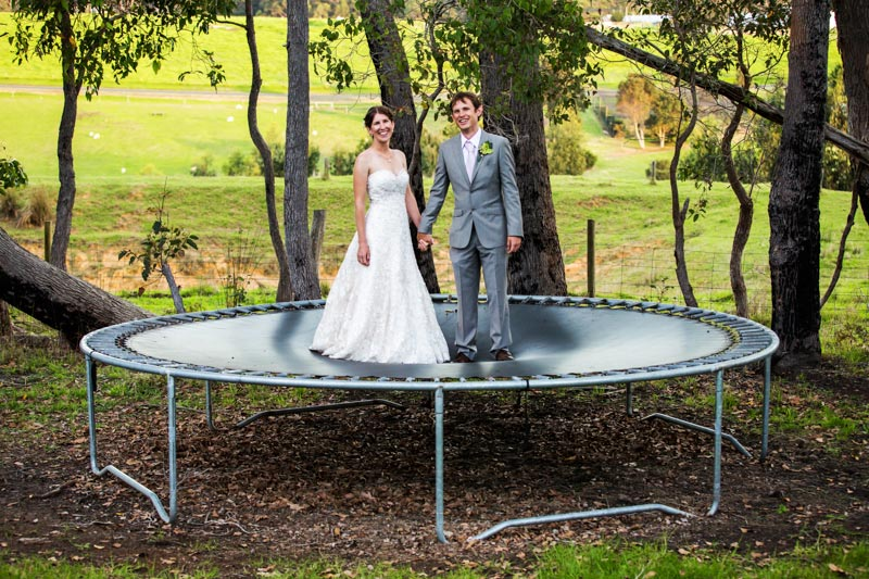 south west wedding photographer image of bride and groom standing on trampoline