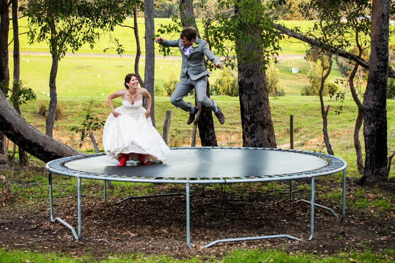 south west wedding photographer image of bride and groom jumping on trampoline