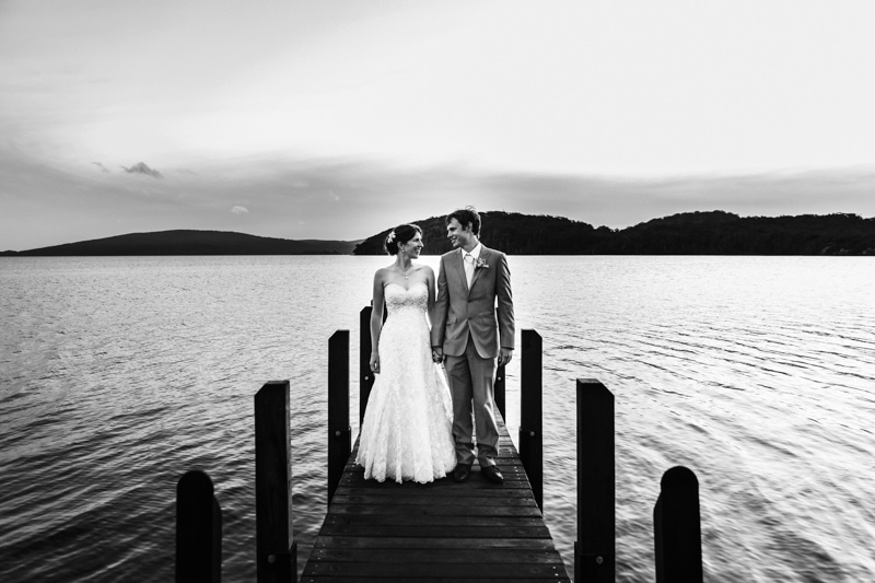 south west wedding photographer image of bride and groom holding hands on jetty