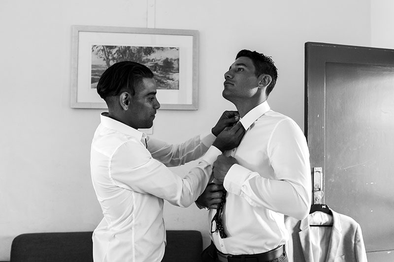 perth wedding photographer rottnest island wedding image of groomsman helping groom with his bowtie