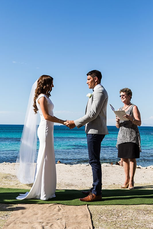 perth wedding photographer rottnest island wedding image of bride and groom at ceremony holding hands on the beach