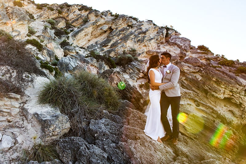 perth wedding photographer rottnest island wedding image of bride and groom standing on rocks on rottnest island