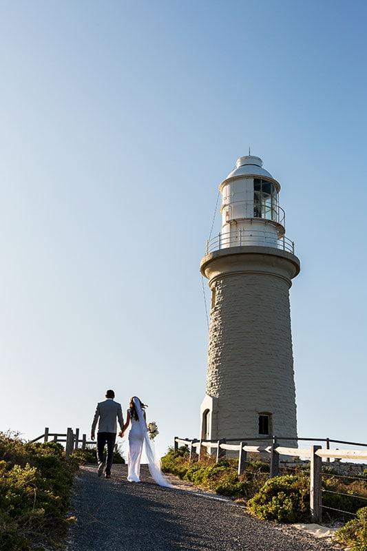 perth wedding photographer rottnest island wedding image of bride and groom walking towards light house on rottnest island