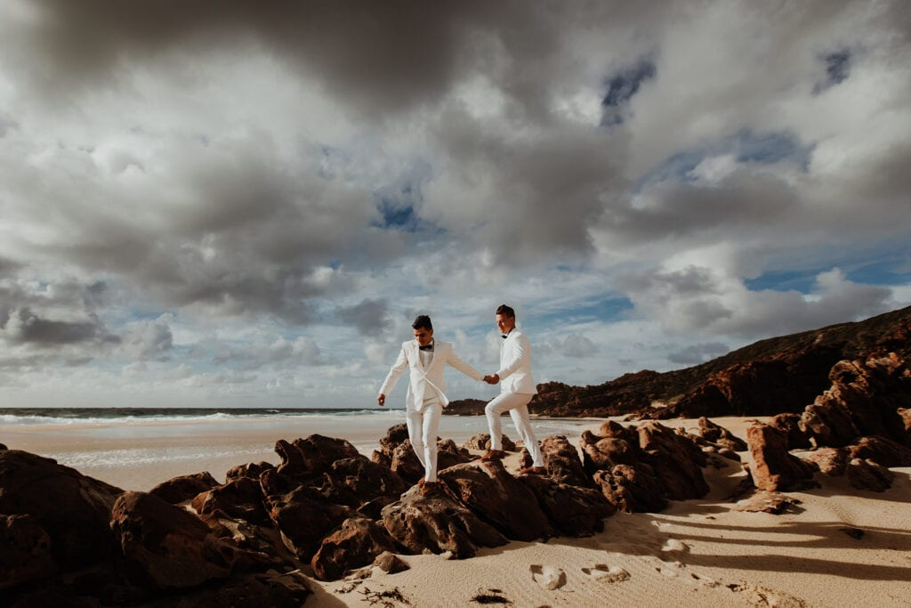 same sex couple in white suits walking on rocks at Perth wedding