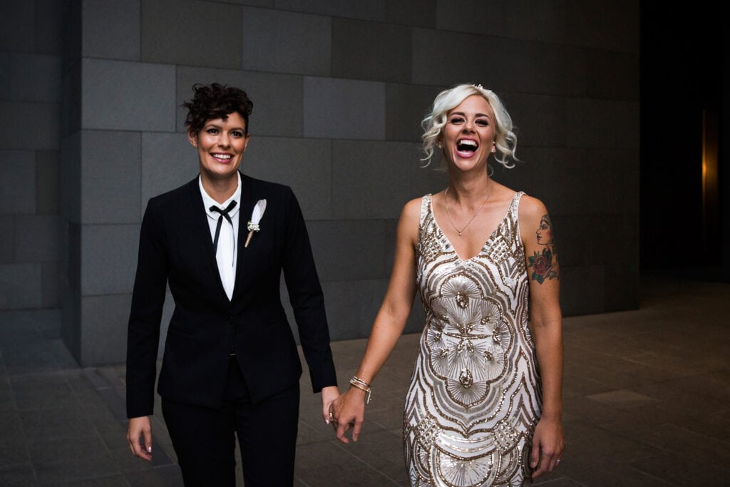 same sex couple holding hands laughing