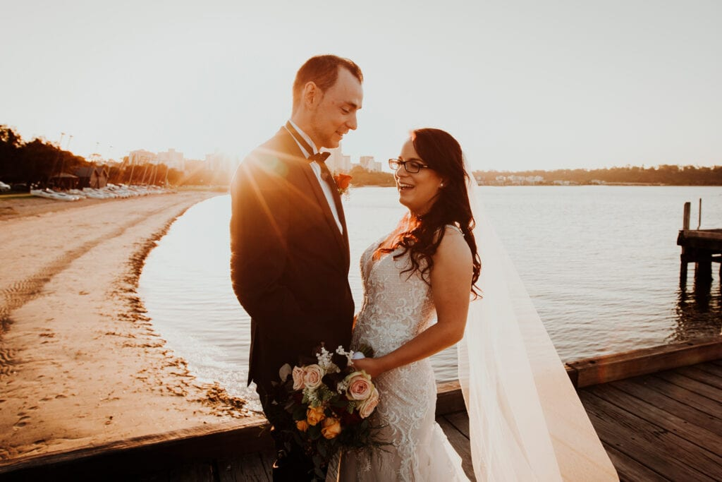 couple laughing at sunset on jetty at Perth wedding