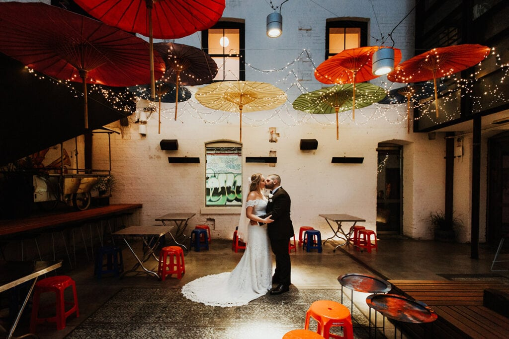 bride and groom kissing under colourful umbrellas in Perth city